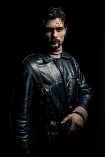 A man in a black leather coat and a brown sweater. Mercenary with a gun. He wears medium-length hair, a mustache and a beard. Hair is wet and glisten in the rays of light. Brutal look like a comic book hero. Pensive look, serious guy. Low key portrait. Silhouette of a man on a black background. Selective lighting. Studio photography. Portrait Black Leather Serious One Person One Man Only Gun Young Men Young Adult Facial Hair Studio Shot Indoors  Beard Waist Up Standing Clothing Men Black Background Front View Casual Clothing Jacket Looking Leather Jacket Contemplation Real People