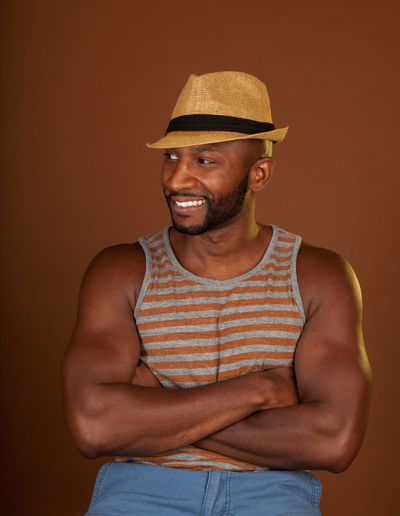 Smiling Man Wearing Hat Against Colored Background