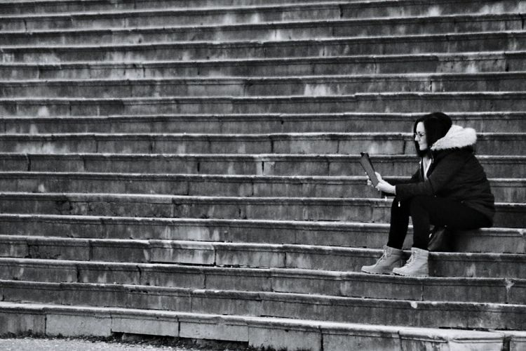 Full length of woman using digital tablet while sitting on steps