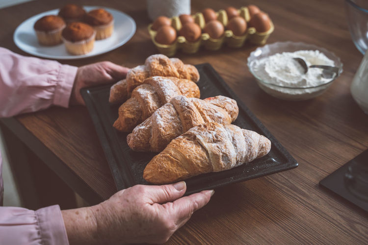 Cropped hand of senior woman holding croissant in tray