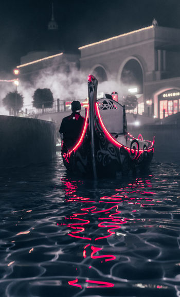 Illuminated red boat in canal in city