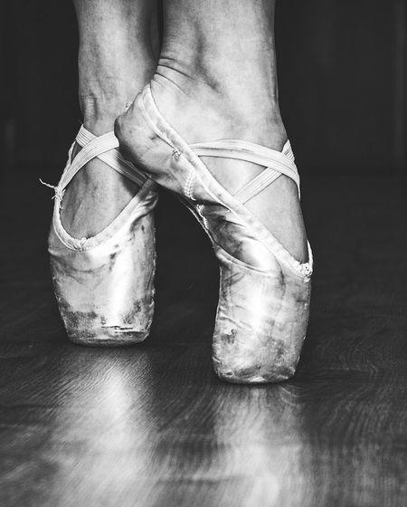Low section of ballerina dancing on floorboard