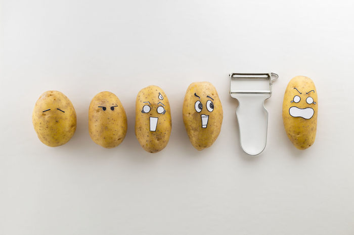 Fresh potatoes with cartoon style faces laying on white surface are scared from a peeler Anime Cooking Crazy Face Funny Horror Brown Cartoon Character Close-up Crazy Fate  Food Funny Faces Group Kitchen Utensils No People Organic Peeler Potatoes Preparing Food Scared Scared Face Style White Background Yummy