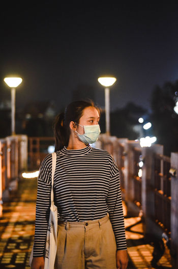 Woman wearing mask in city at night