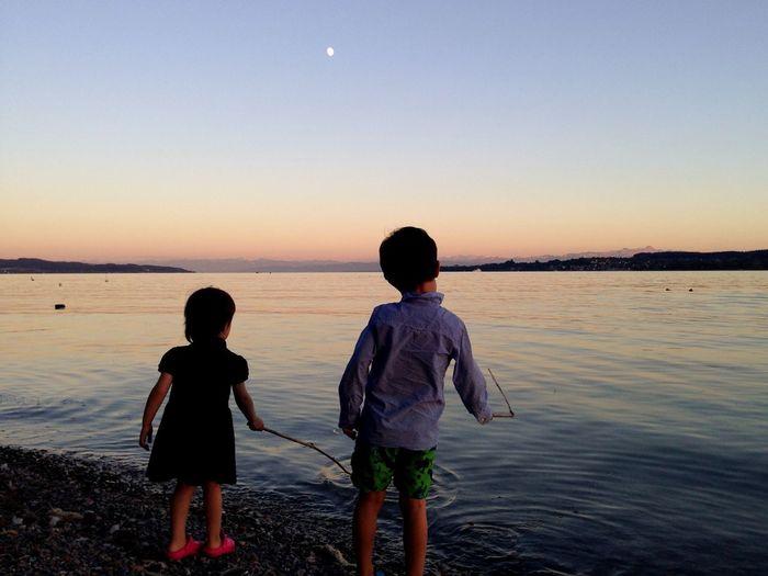 Siblings Fishing At Riverbank Against Sky During Sunset