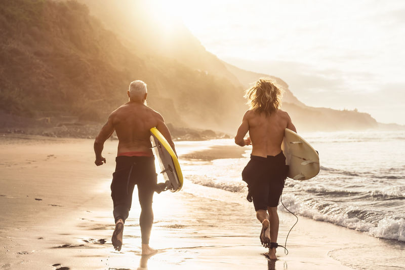 Rear view of shirtless men carrying surfboards while walking at beach