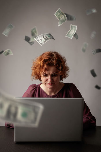 Paper currencies falling on mature woman using laptop over desk
