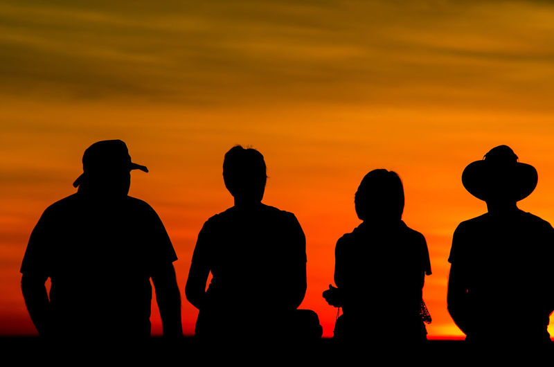 Silhouette friends sitting on bench against sky during sunset