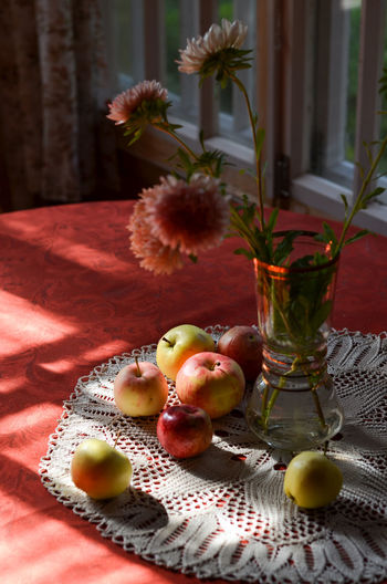 Appples and flowers in vase on table.