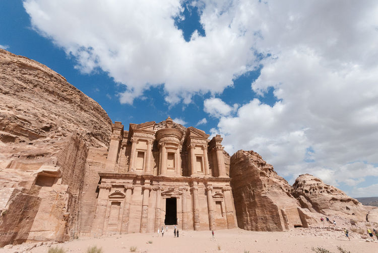 Low angle view of the monastery at petra in jordan against a blue sky with clouds