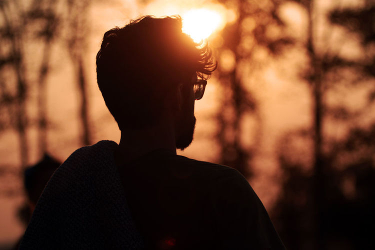 Close-up Focus On Foreground Headshot Leisure Activity Lifestyles Men Nature One Person Outdoors Portrait Profile View Real People Side View Silhouette Sky Standing Sunlight Sunset Young Adult Young Men