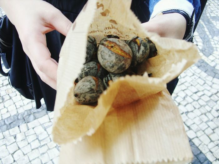Person Showing Roasted Chestnut In Paper Bag