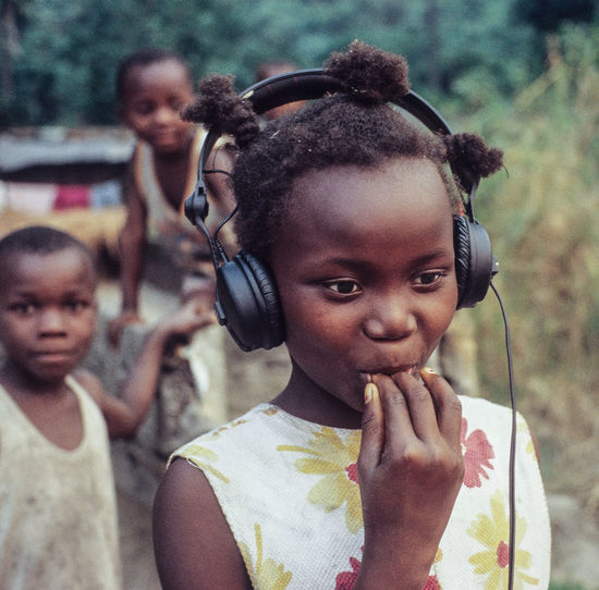 The girl with the headphone, listening the first time in her life to her own voice after giving me an interview for TV. childhood portrait DR Congo Natural Beauty unspoiled Innocence girls Interview record The Week on EyeEm Listening Childhood Portrait DR Congo Natural Beauty Unspoiled Innocence Girls Interview Record Analogue Photography Leica M6 Slidefilm African Colors This Is Africa Interested Congolese Village Shygirl