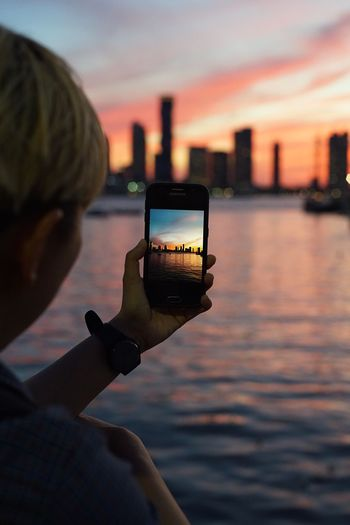 Cropped Image Of Boy Photographing City Skyline Through Smart Phone During Sunset