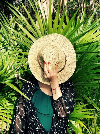Fashionable woman hiding face with hat while standing amidst plants