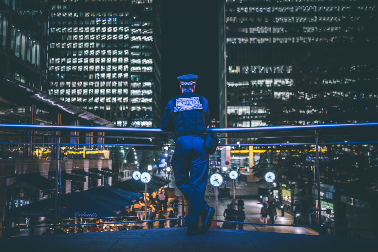 Security officer standing on bridge while looking at illuminated city during night