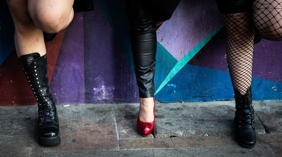 Low section of women in high heels standing against wall
