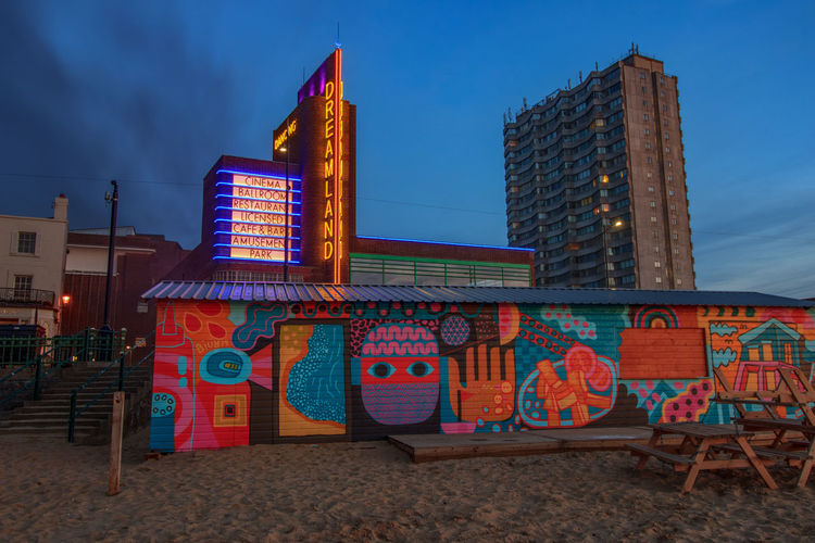 Dreamland, Margate Seafront, Margate, Kent, England. Architecture Building Exterior Built Structure Sky City Nature No People Building Multi Colored Cloud - Sky Illuminated Land Outdoors Blue Office Building Exterior Travel Destinations Dusk Beach Day Low Angle View Skyscraper Modern Seafront Vivid International Tourism Garden Of England Getty Images EyeEM Beach Photography Dreamland Beach Hut Swimming Sunset Architecture Council Flats