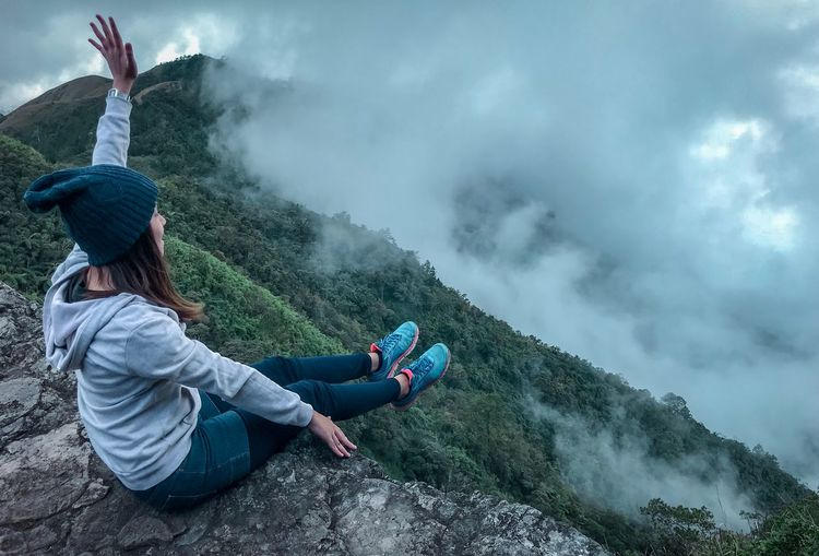 Full Length Of Carefree Young Woman Sitting On Cliff During Foggy Weather