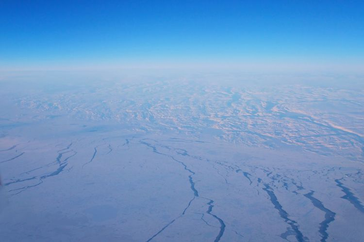 Aerial view of snowcapped landscape against blue sky