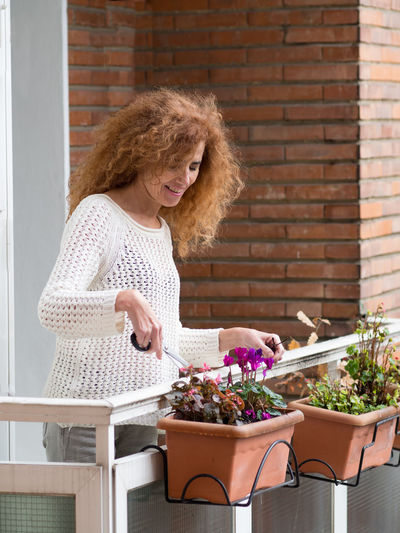 Close-up of woman holding flower pot against brick wall