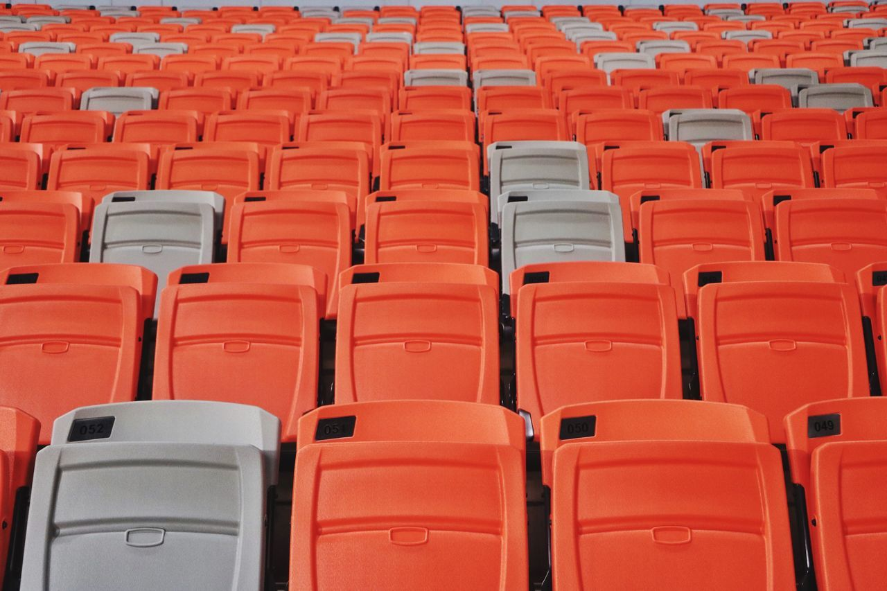 empty, in a row, seat, chair, absence, repetition, no people, side by side, red, orange color, backgrounds, large group of objects, full frame, indoors, arts culture and entertainment, order, stadium, auditorium, arrangement, bleachers