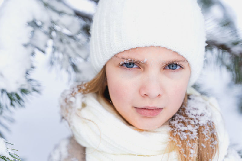 Portrait of young woman in hat during winter