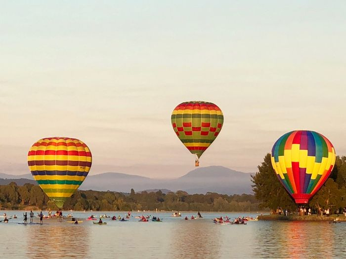 Hot air balloons flying over lake against sky during sunset