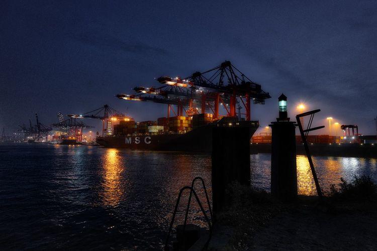 Illuminated pier by harbor against sky at night
