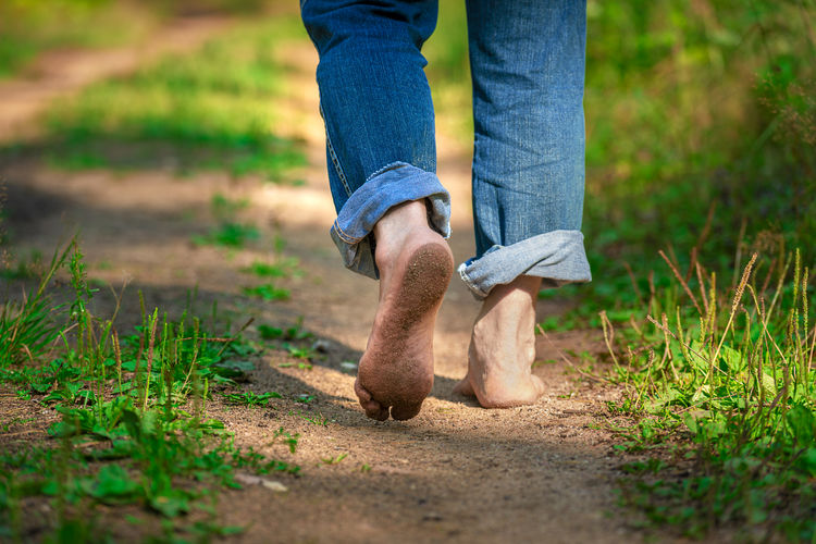 Low section of man walking barefoot in forest