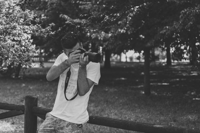 Boy photographing with mobile phone in park