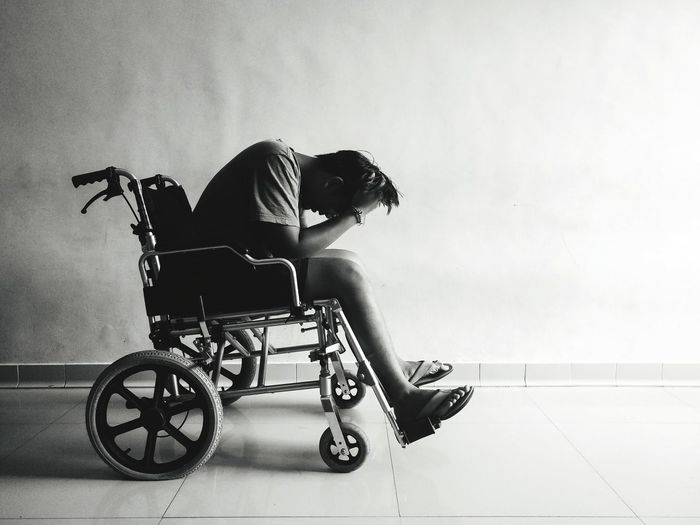 Tensed Man Sitting On Wheelchair At Home