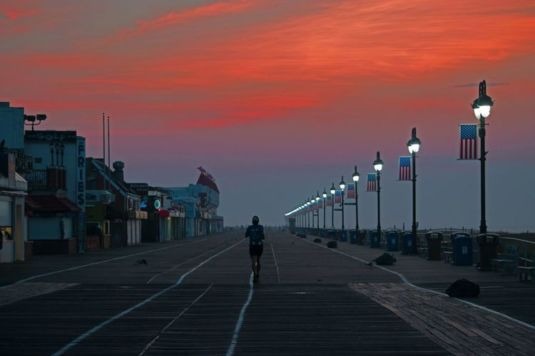Battle Of The Cities Cloud Diminishing Perspective Dramatic Sky Footpath Illuminated In A Row Lamp Post Lighting Equipment New Jersey Ocean City, NJ Orange Color Outdoors Pedestrian Walkway Runner Runnergirl Runners Sky Street Light The Way Forward Tranquil Tranquil Scene Tranquility USA Walking The Great Outdoors - 2017 EyeEm Awards Sommergefühle