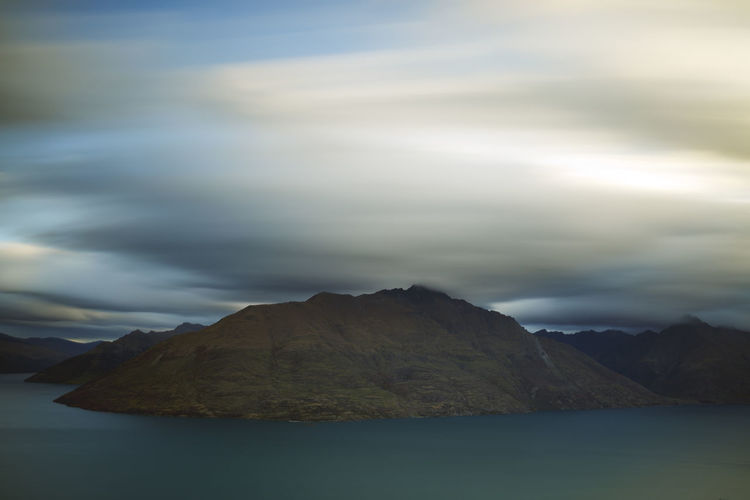 A long exposure shot of clouds passing over mountains. Beauty In Nature Day Lake Landscape, Travel, People, Freedom, Mountain, View, Adventure, Journey, Tourism, Backpack, Trip, Nature, Hill, Tourist, Top, Snow, Outdoor, Beautiful, Clouds, Peak, Valley, Wanderlust, Lifestyle, Explore, Scenic, Lake, Relaxing, Leisure, Sky, Mountains, M Mountain Mountain Range Nature No People Outdoors Scenics Sky Tranquil Scene Tranquility Water Waterfront