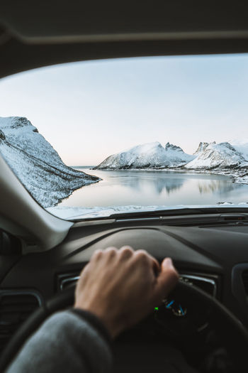 Cropped Hand Of Person Driving Car Against Mountains
