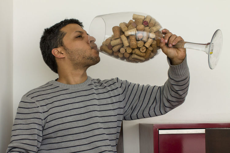 Man Drinking Cork Stoppers From Wineglass Against Wall