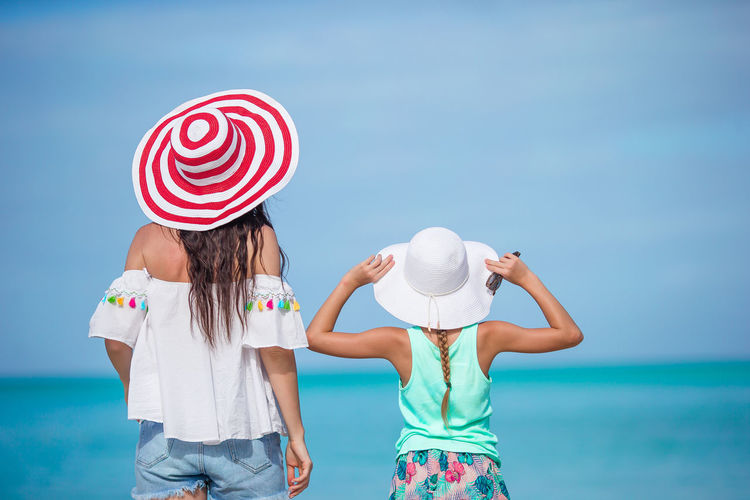 Rear view of women standing by sea against sky