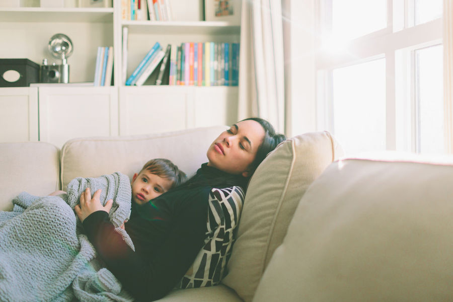 Mother Bonding Casual Clothing Child Day Domestic Life Home Interior Indoors  Leisure Activity Lifestyles Living Room Love Parent Real People Relaxation Sleep Sofa Tired Togetherness Two People Young Adult