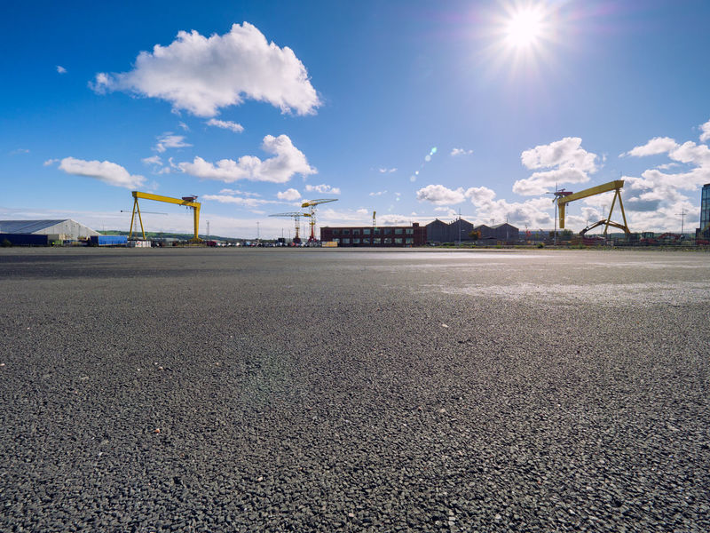 Empty road surface against blur Belfast city landmark background No People Urban Skyline Landsacpe Nobody Business Water Belfast Blue Northern Ireland Architecture Building Exterior Built Structure City Day Modern Clear Sky Outdoors Sky Skyscraper Bridge Crane - Construction Machinery Shipyard Titanic Belfast Titanic Quarter