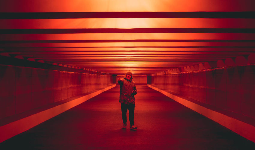 Man Standing In Red Illuminated Tunnel