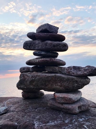 Stack of stones on beach against sky during sunset