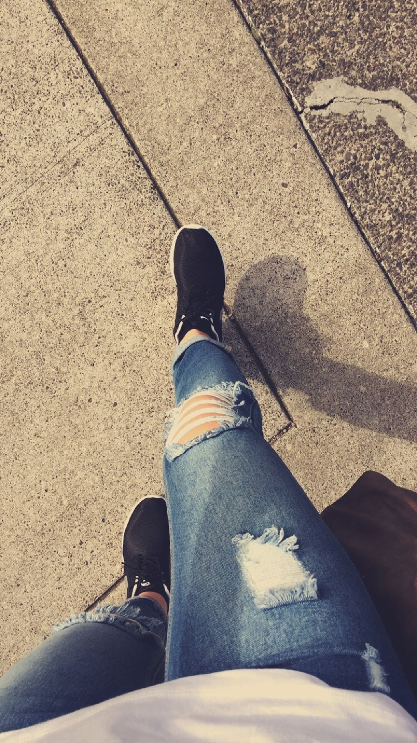 low section, person, personal perspective, shoe, lifestyles, standing, high angle view, men, street, jeans, road, shadow, leisure activity, sunlight, casual clothing, footwear, human foot