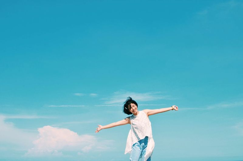 Happy Asian woman with sky and beach background,copy space, Adult Adults Only Arms Outstretched Arms Raised Blue Cloud - Sky Copy Space Day Front View Happiness Human Arm Human Body Part Limb Low Angle View One Person One Woman Only One Young Woman Only Only Women Outdoors People Sky Standing Young Adult Young Women