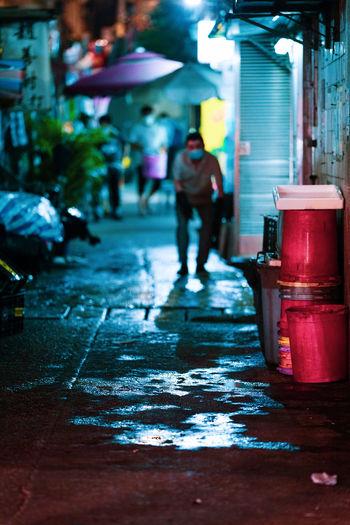 Rear view of man walking on wet street
