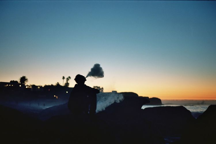 Silhouette man emitting smoke from mouth against clear sky during sunset