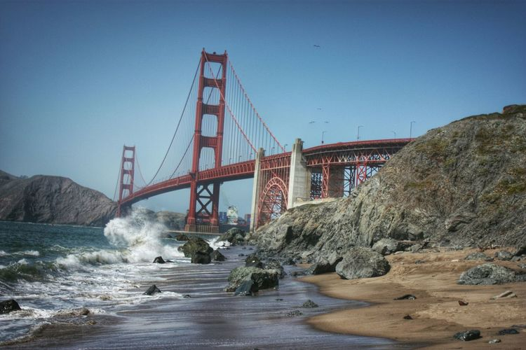 Low angle view of golden gate bridge over bay against sky