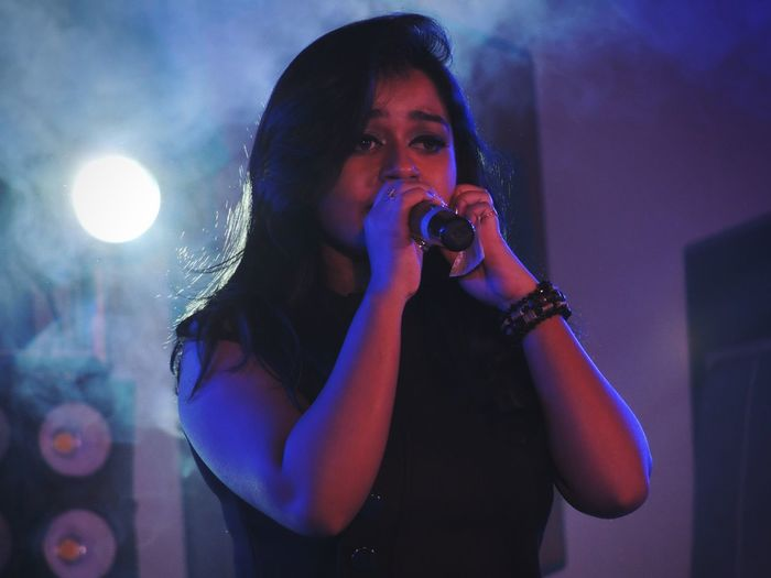 Close-Up Of Young Woman Singing On Stage