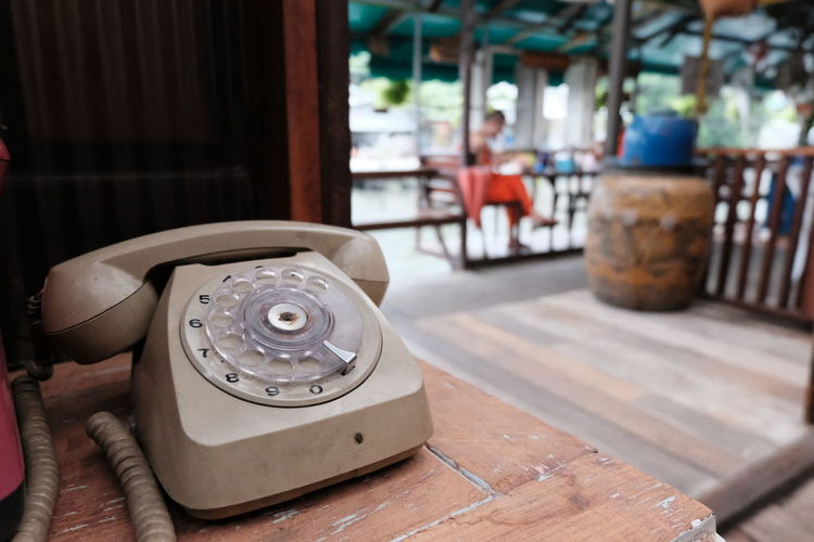 Close-up of old telephone booth on table