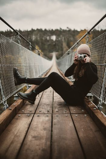 Young woman photographing while sitting on footbridge