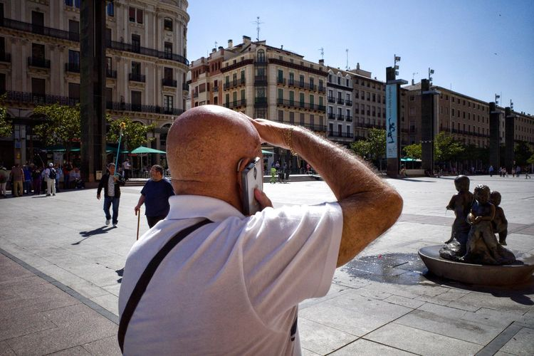 Rear view of man photographing statue on street in city